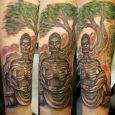 En tatuering av en mager buddha som mediterar